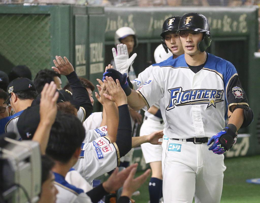 1回、先制2ランを放ちナインに迎えられる日本ハム・大田=東京ドーム