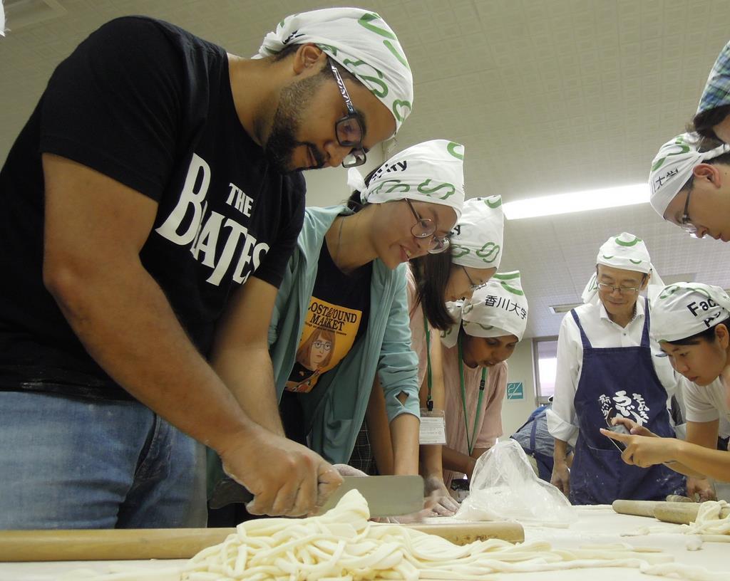 包丁でうどんの生地を切る留学生=8月、高松市の香川大