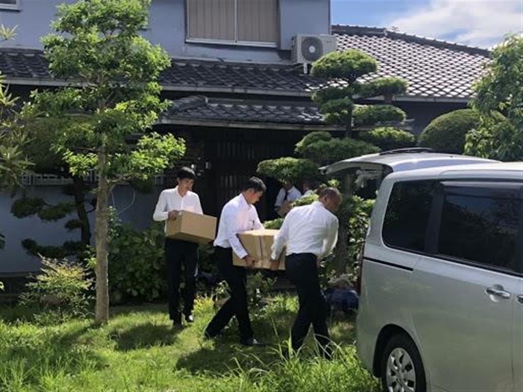 竹山修身氏の自宅から押収物を運び出す大阪地検の係官=12日午後、堺市北区