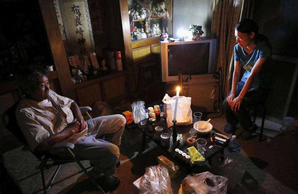 台風15号の影響による停電で、暗がりの中ろうそくの明かりで過ごす親子=13日午後、千葉県館山市
