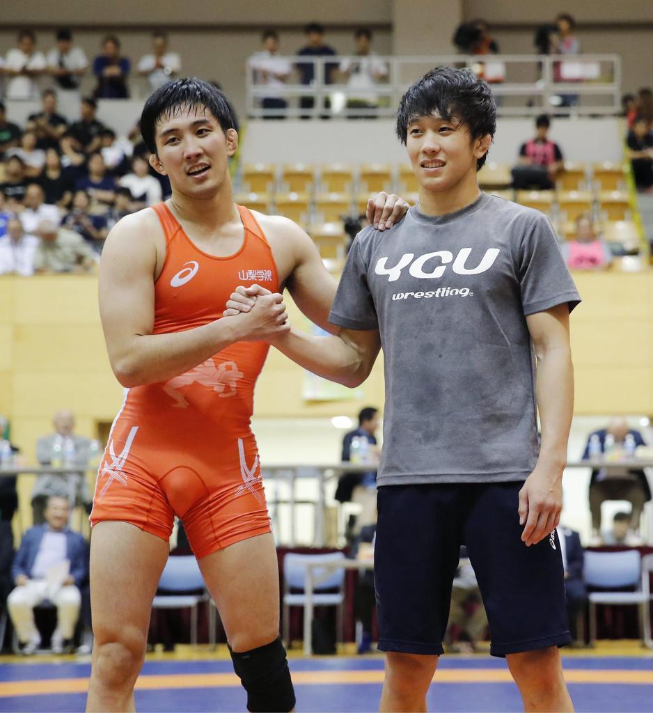 世界選手権代表入りを決め、握手する兄の乙黒圭祐(左)と弟の拓斗=和光市総合体育館