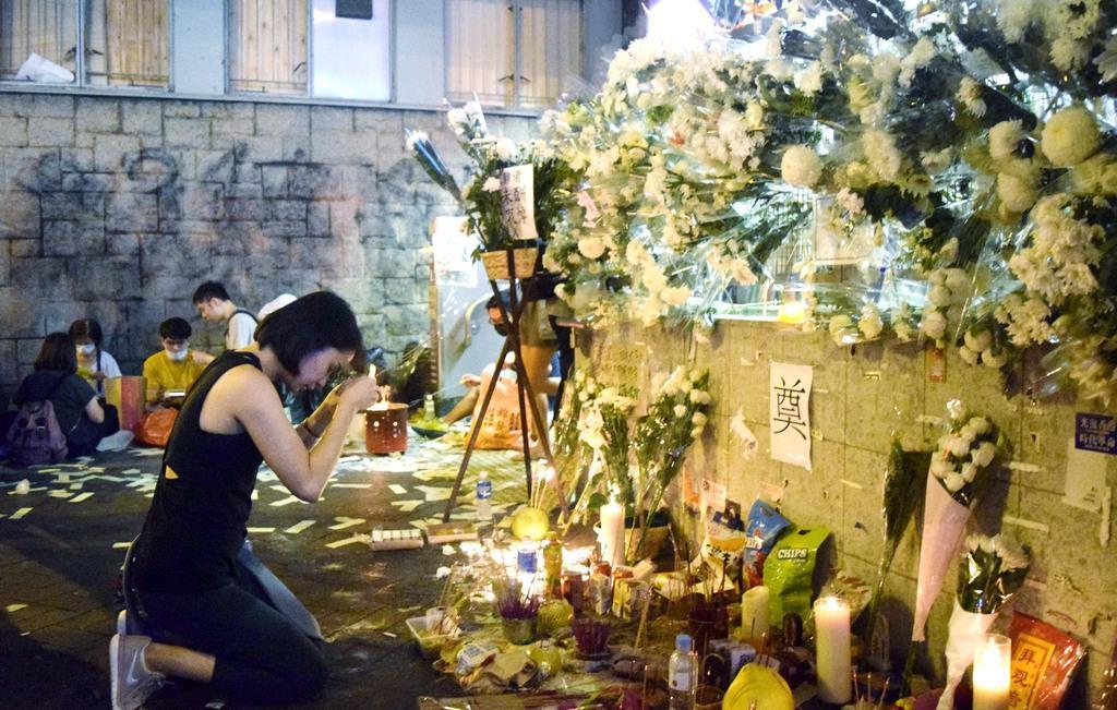 香港・九竜地区の地下鉄太子駅の出口に設けられた「祭壇」に線香を手向ける女性=12日夜(田中靖人撮影)