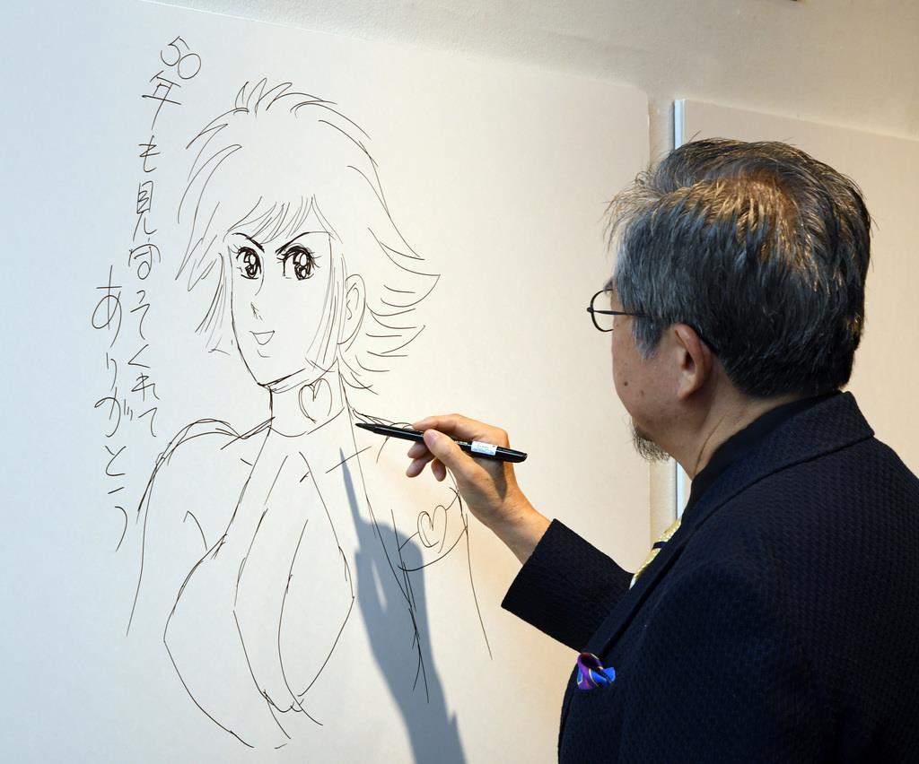 「永井GO展」のメッセージボードにキューティーハニーを描く永井豪=13日午後、東京・上野公園の上野の森美術館(酒巻俊介撮影)