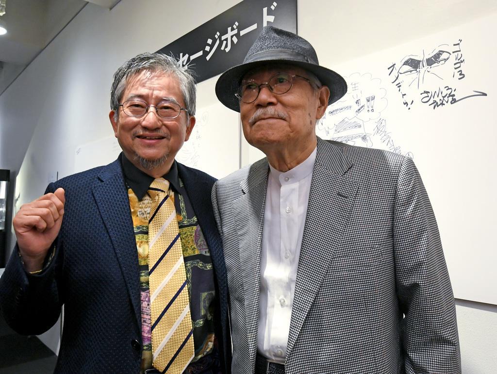 メッセージボードにゴルゴ13を描いたさいとうたかを(右)と記念撮影する永井豪=13日午後、東京・上野公園の上野の森美術館(酒巻俊介撮影)