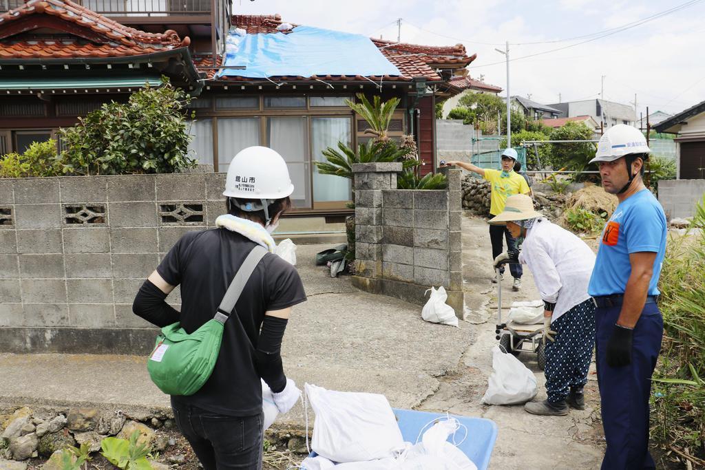 屋根に張るブルーシートを押さえる土のうを運ぶボランティアら=14日午前、千葉県館山市