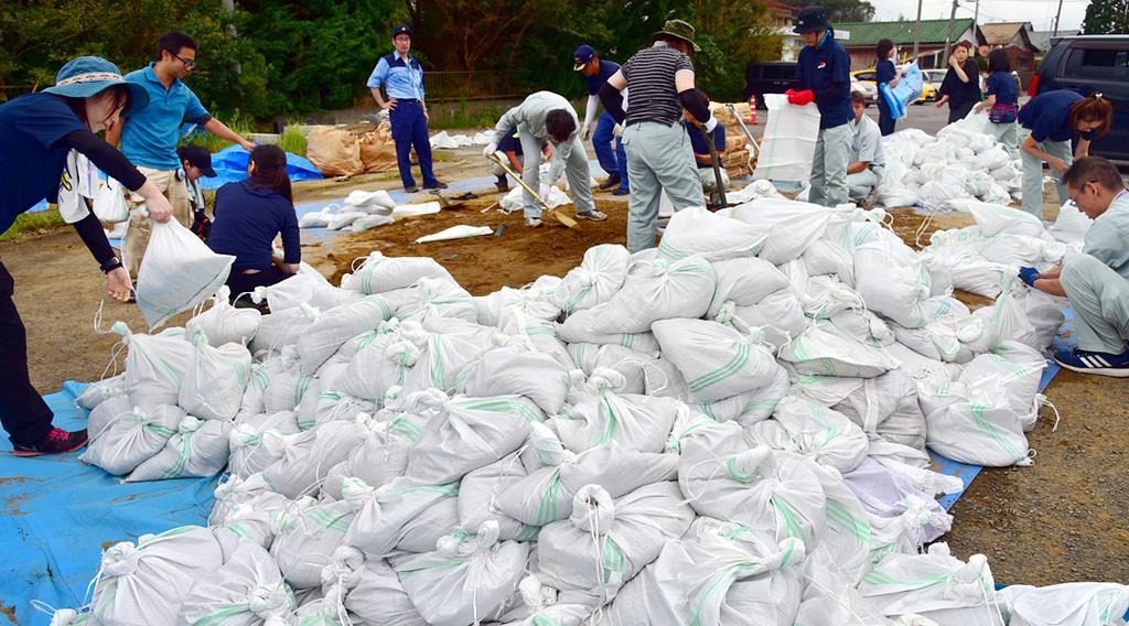 台風で破損した屋根の応急処置に使う土嚢作りに県外からのボランティアも参加した=14日、千葉県多古町役場(城之内和義撮影)