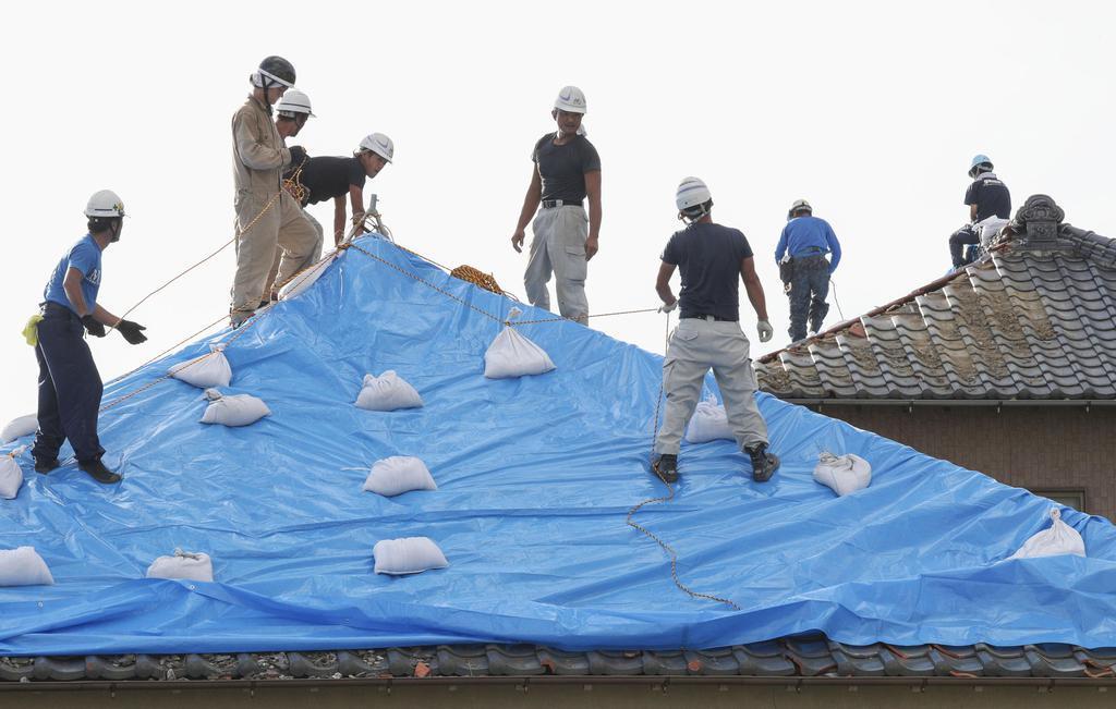 台風15号の被害にあった住宅で、屋根にブルーシートを張る作業をする人たち=14日午後、千葉県館山市