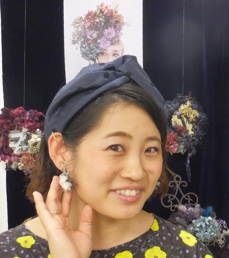 「フラワーサイクリスト」の河島春佳さん。自作のイヤリングが小さな花束のよう