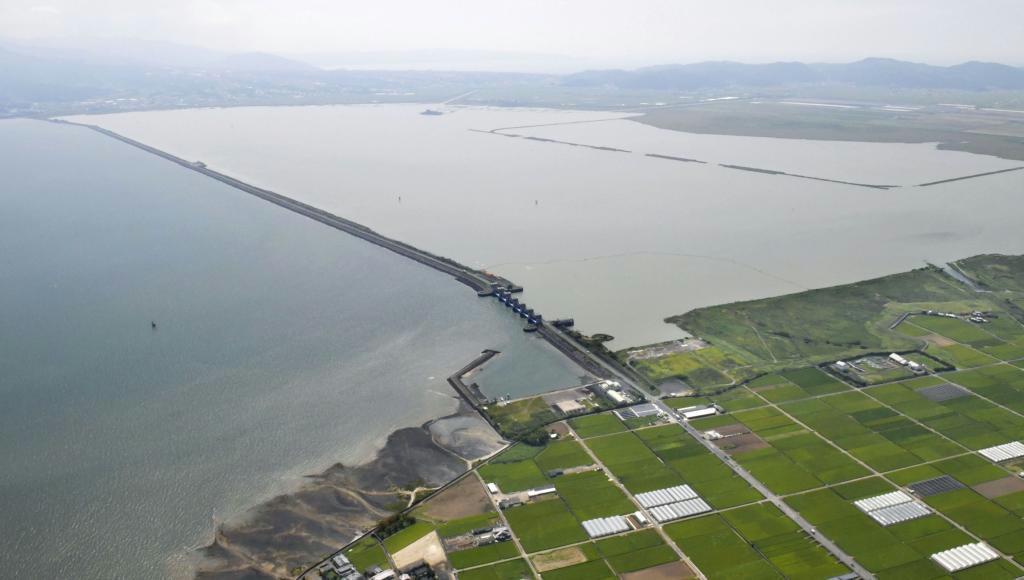 国営諫早湾干拓事業の潮受け堤防で仕切られた干拓地側調整池(奥)と有明海。中央は北部排水門