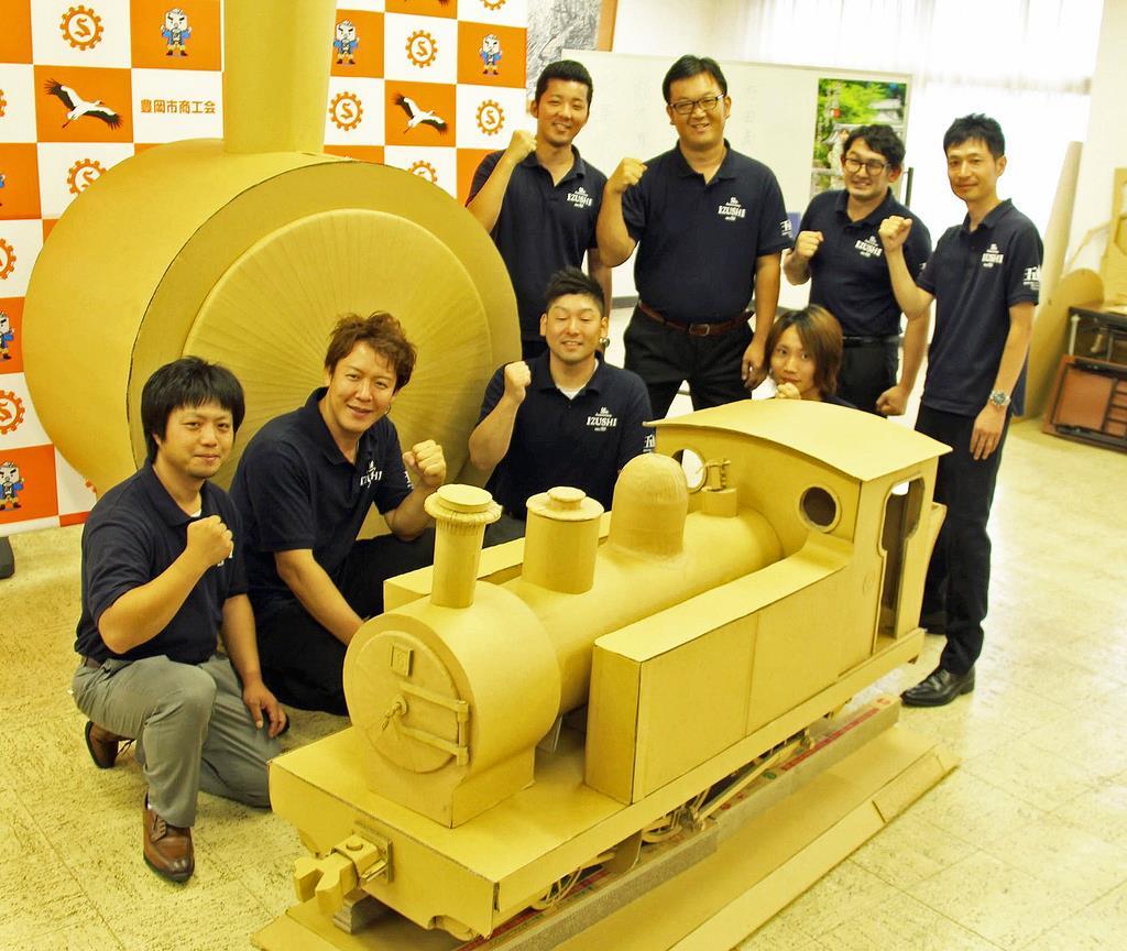 段ボールで実物大の蒸気機関車を再現した若手経営者ら。手前は4分の1の模型=豊岡市出石町