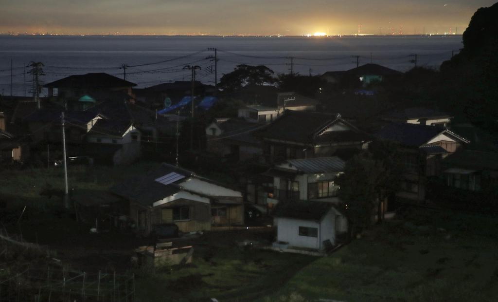 大規模停電を引き起こした台風15号の通過から1週間。いまだに明かりが戻らない千葉県富津市とは対照的に、対岸の東京湾岸は明かりがともっていた=16日夜