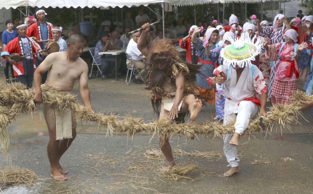 稲刈りの様子を再現する男性ら