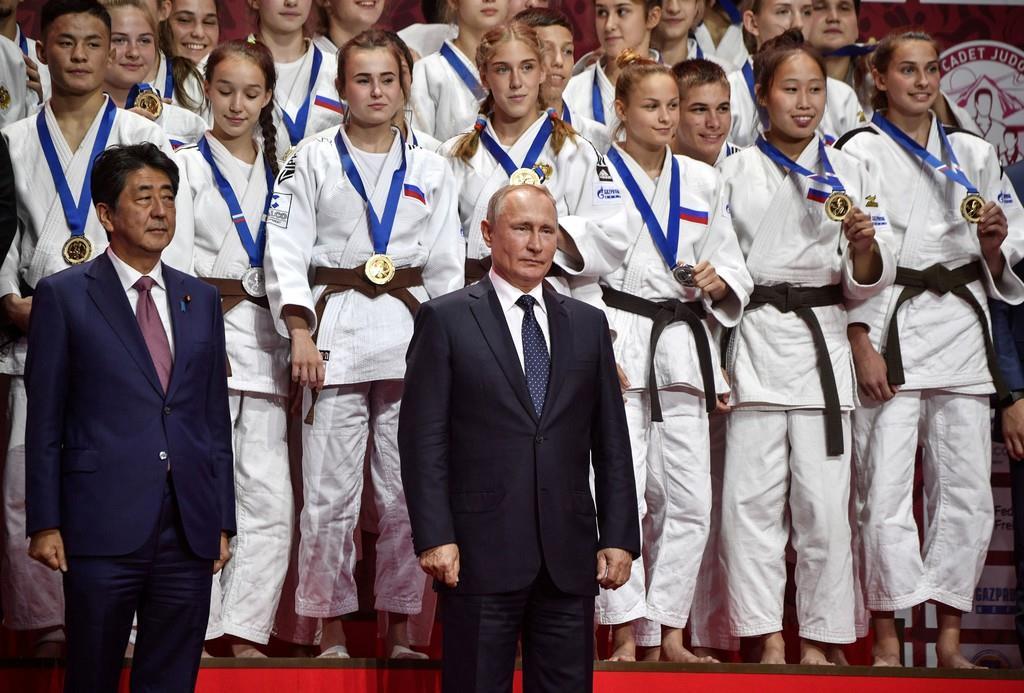 東方経済フォーラムに合わせて開かれたU-18柔道トーナメントを観覧し、メダリストらの前で記念撮影に応じる安倍晋三首相(前列左)とプーチン露大統領(同右)=5日、ウラジオストク(ロイター)