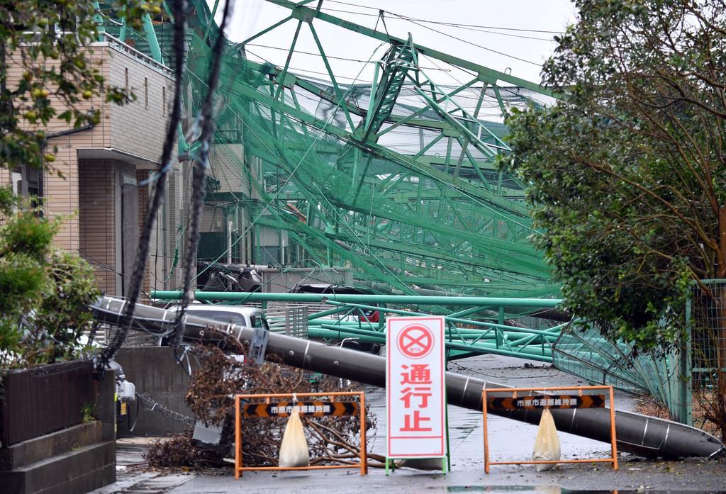台風15の影響で住宅に倒れたゴルフ練習場の鉄柱とネット=16日午前、千葉県市原市(鴨川一也撮影)