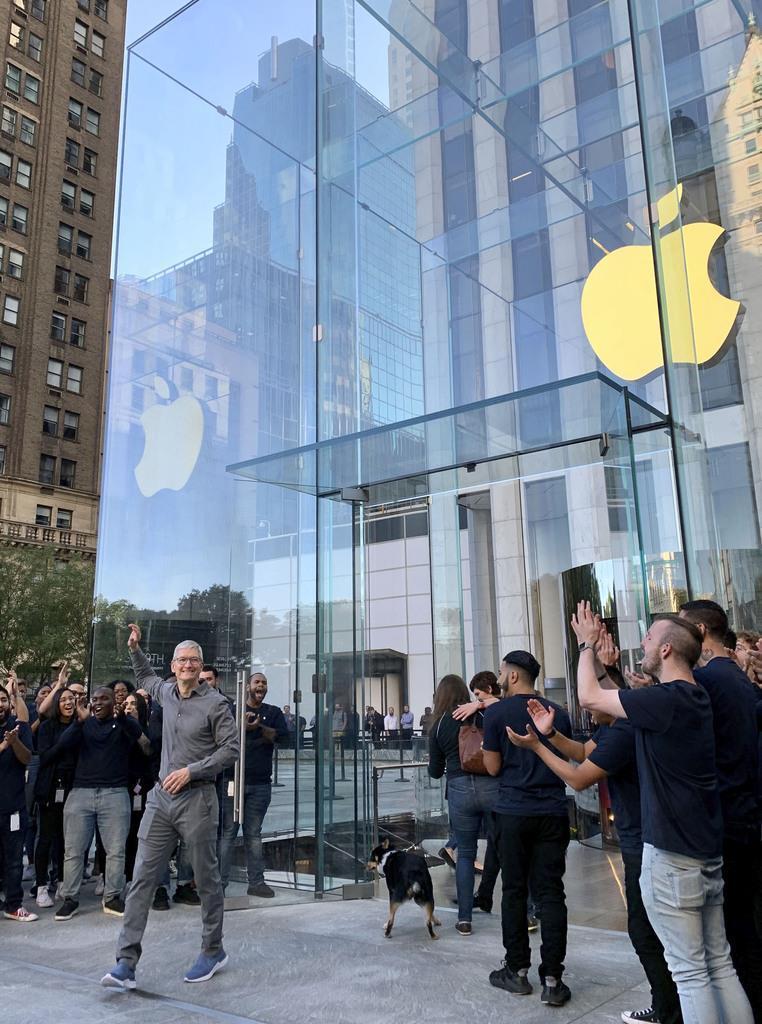 旗艦店の入り口で手を振る米アップルのティム・クックCEO(左手前)=ニューヨーク(共同)