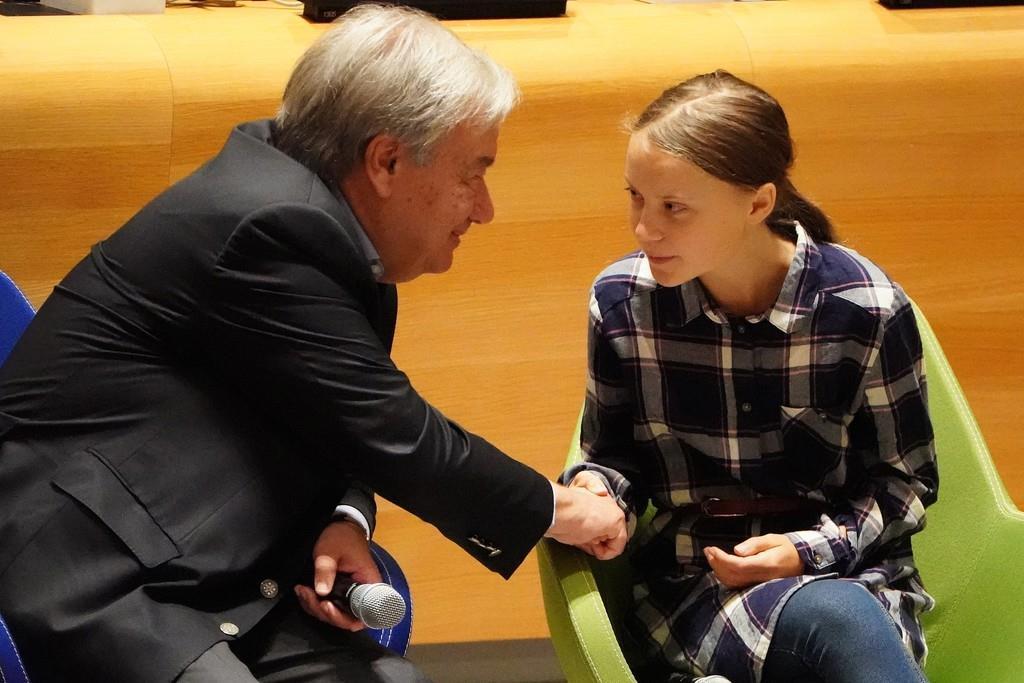 気候行動サミットを主宰する国連のグレテス事務総長は、スウェーデンの環境活動家の少女、グレタ・トゥーンベリさんと握手を交わした=21日(ロイター)