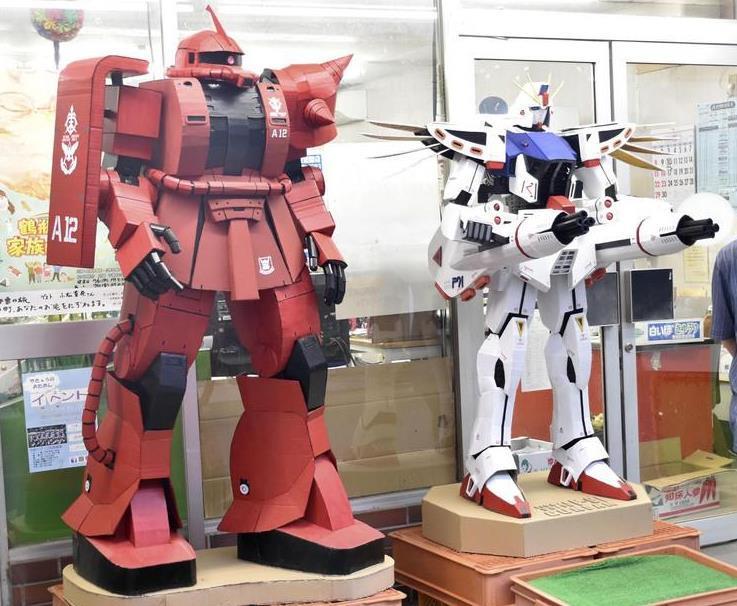 青果店「岡林商店」の店先に登場した段ボール製のシャア専用ザク(左)とガンダムF91=高知県いの町