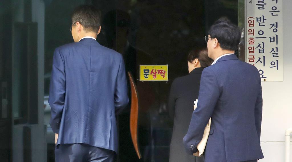 家宅捜索のため、韓国のチョ・グク法相の自宅があるマンションに入る検察関係者=23日、ソウル(聯合=共同)