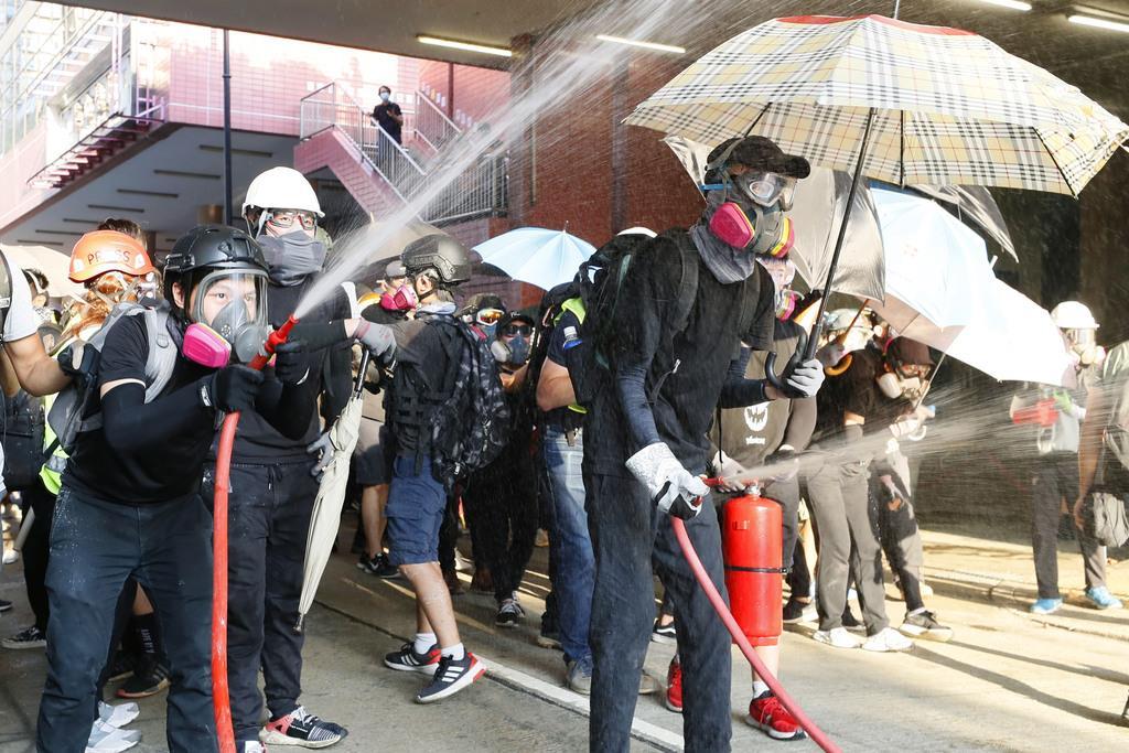 香港の新界地区で放水して警官隊に抵抗する若者ら=21日(共同)
