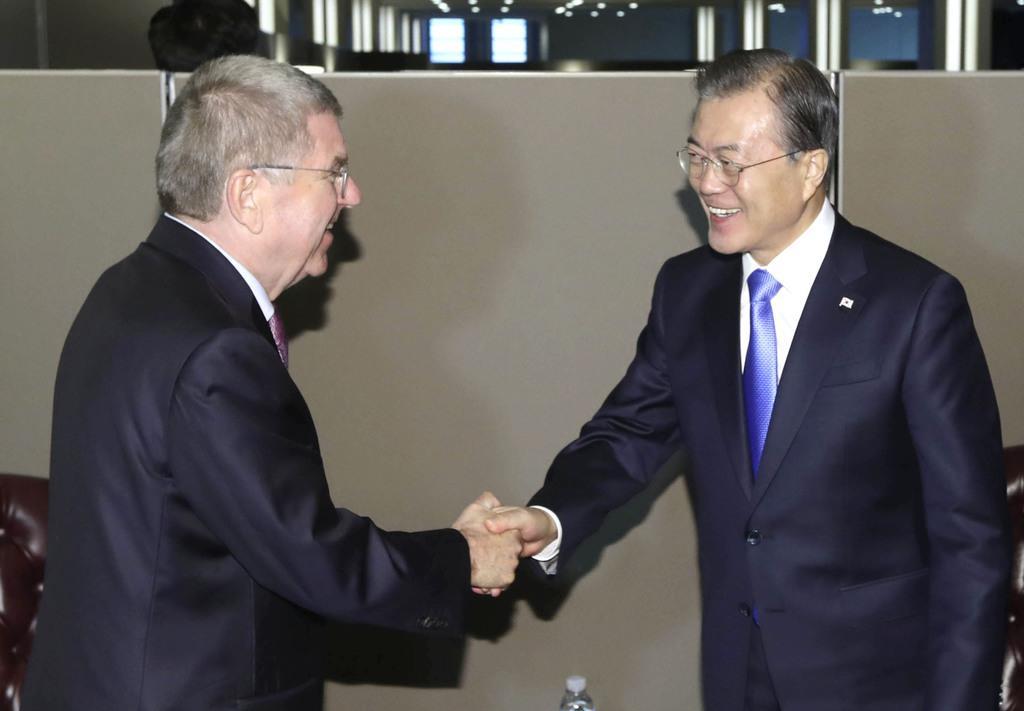 24日、米ニューヨークで握手するIOCのバッハ会長(左)と韓国の文在寅大統領(聯合=共同)
