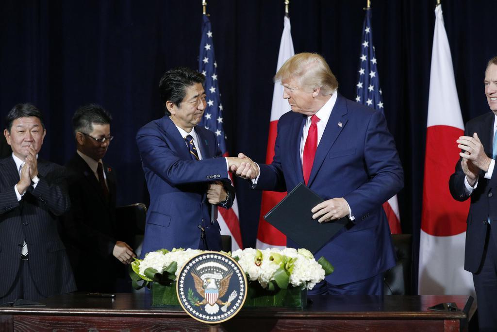 日米貿易協定締結で最終合意し、合意文書への署名を終えて握手する安倍首相(左)とトランプ大統領=25日、米ニューヨーク(共同)