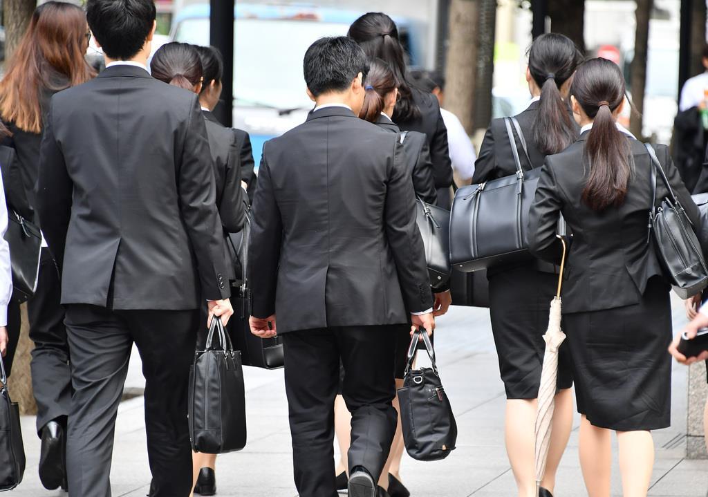 リクルートスーツを着て就職活動する学生