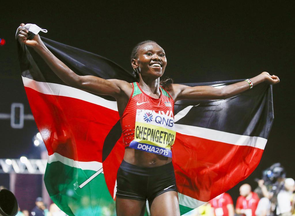 女子マラソンで優勝し、笑顔で国旗を掲げるケニアのルース・チェプヌゲティチ=ドーハ(共同)