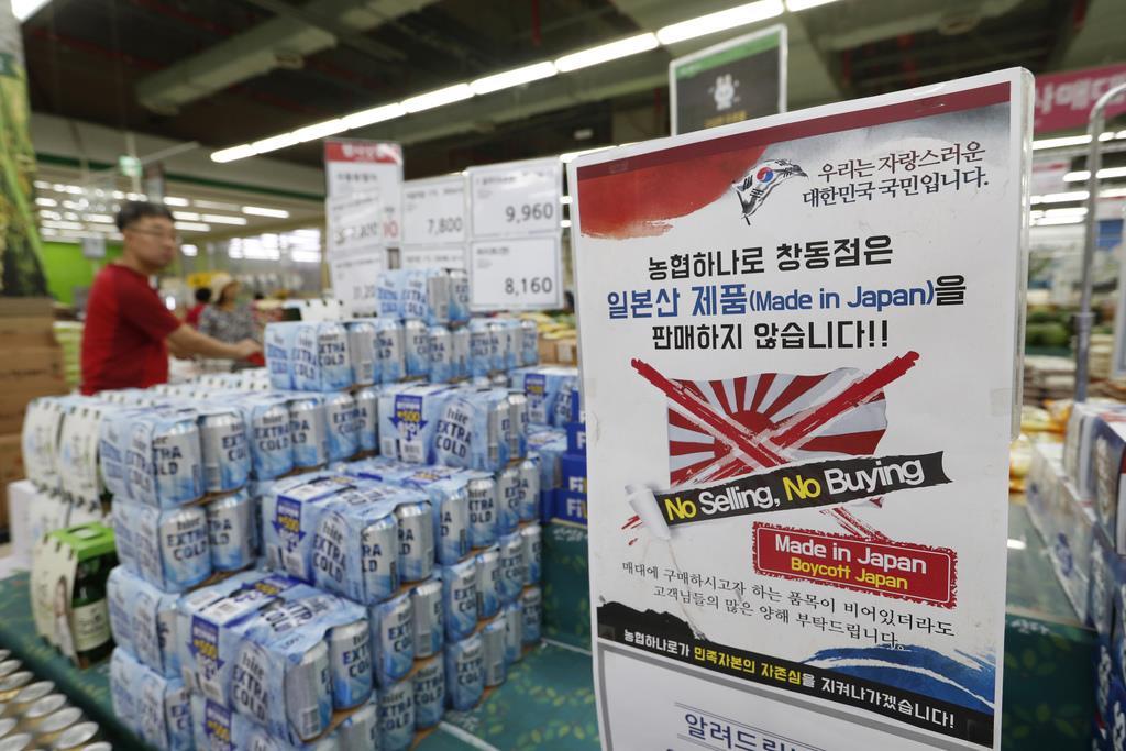 ビールが並ぶ売り場に掲げられた日本製品の不買を知らせる張り紙=7月、ソウル(AP)