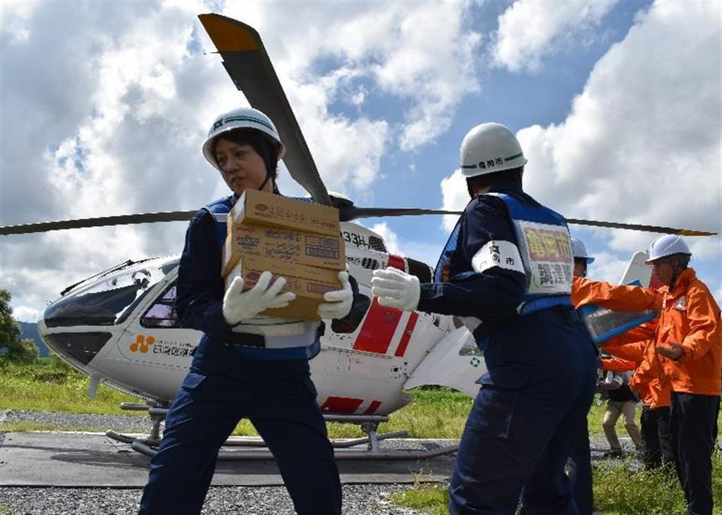 ヘリで運ばれた緊急支援物資を運び出す日清医療食品の社員や亀岡市職員