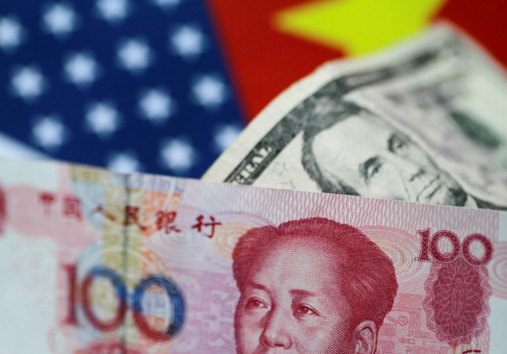 中国の通貨人民元(手前)と米ドル紙幣。人民元相場は米中対立を背景に先行きが見通しにくくなっている(ロイター)