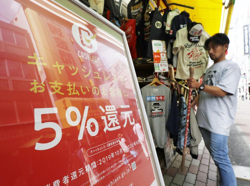 消費税増税に伴い、キャッシュレス決済で5%還元が行われることを告知するポスターを掲示する衣料品店=9月30日午前、東京都台東区
