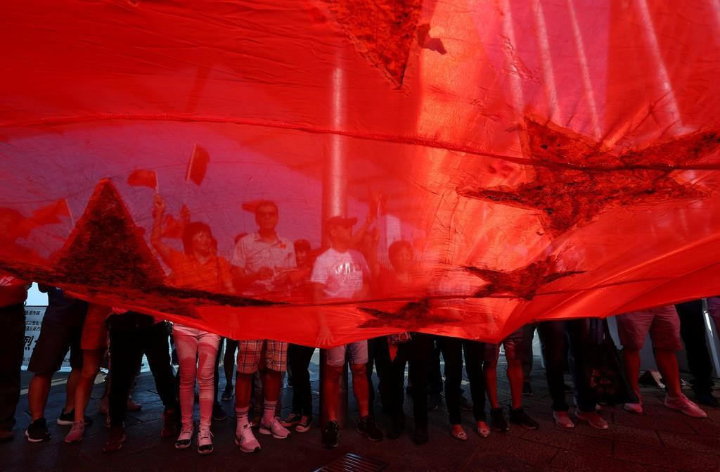 中国建国70周年で国旗を掲げる親中派の香港住民(ロイター)
