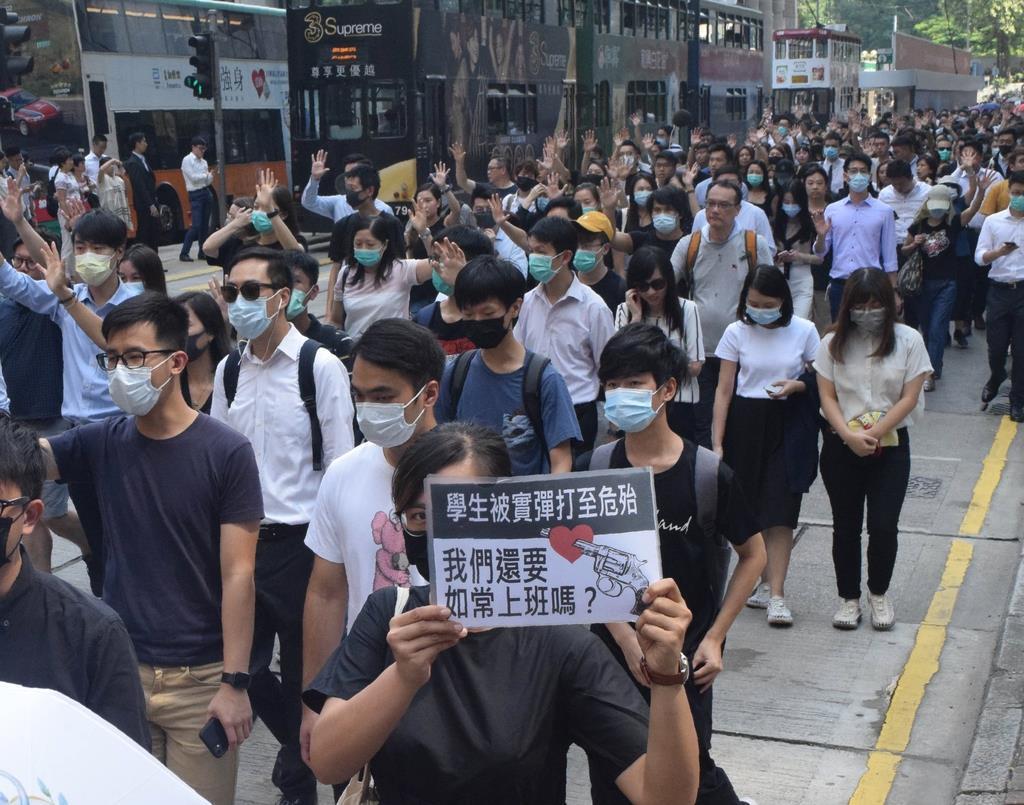 2日、香港の金融街で行われたデモ行進で、生徒を銃撃した警察を批判するプラカードを掲げる参加者(田中靖人撮影)