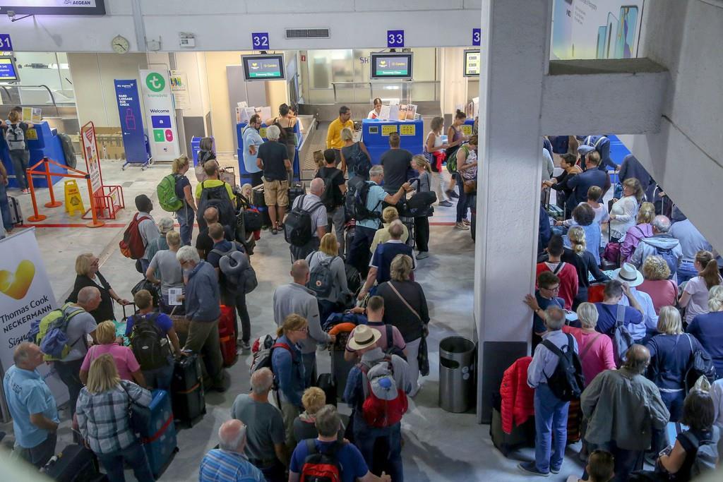 23日、ギリシャのイラクリオン国際空港で並ぶトーマス・クック・グループの利用者。英政府による本国への帰還措置は長時間待たされる混雑が発生した(ロイター)