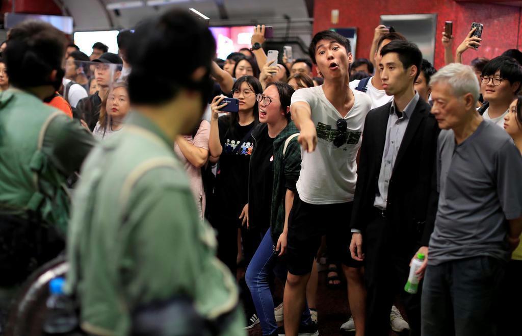 3日、香港の鉄道駅で、警官に向かって抗議の声をあげる若者ら(ロイター)