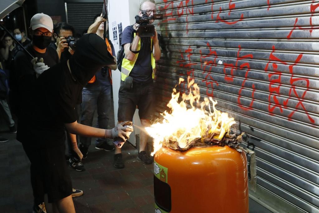 覆面禁止法に反対し、銀行前でごみ箱に放火する若者=4日、香港(共同)