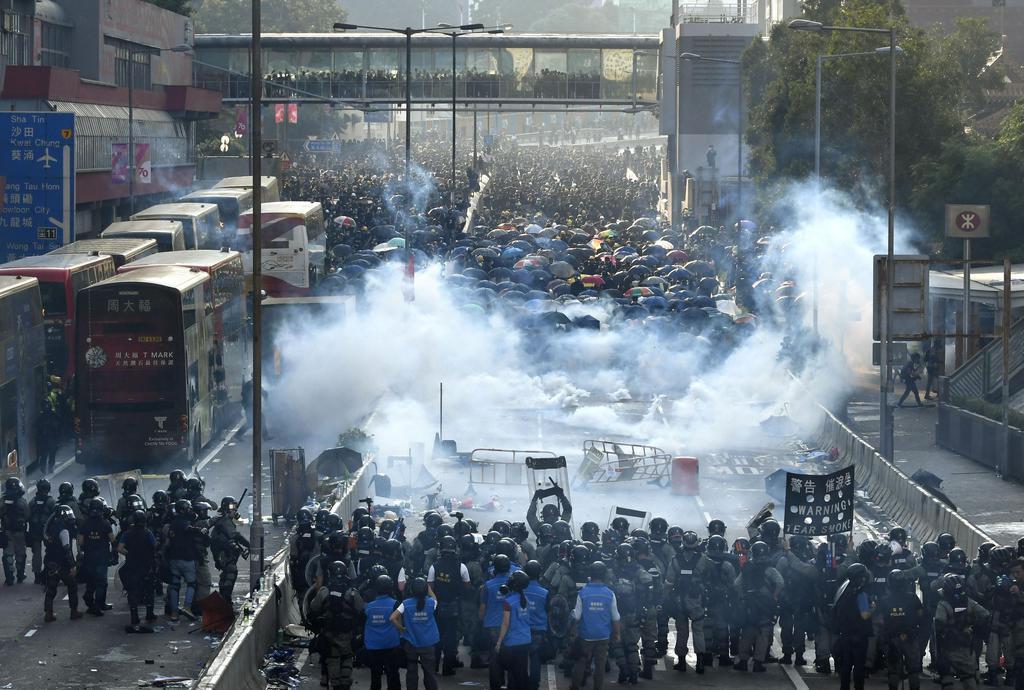 香港で「逃亡犯条例」改正案を発端とした抗議活動をするデモ隊(奥)に、警官隊が催涙弾を撃ち込み現場に立ち込める煙=1日(共同)