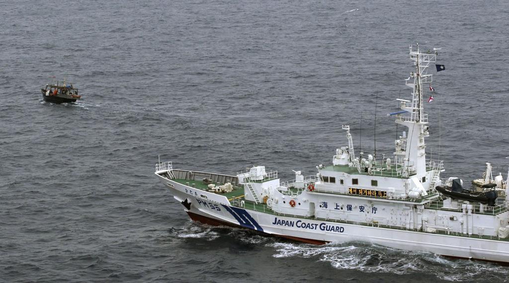 5月、日本海で北朝鮮漁船とみられる木造船(左)に退去警告する海上保安庁の巡視船(海上保安庁提供)