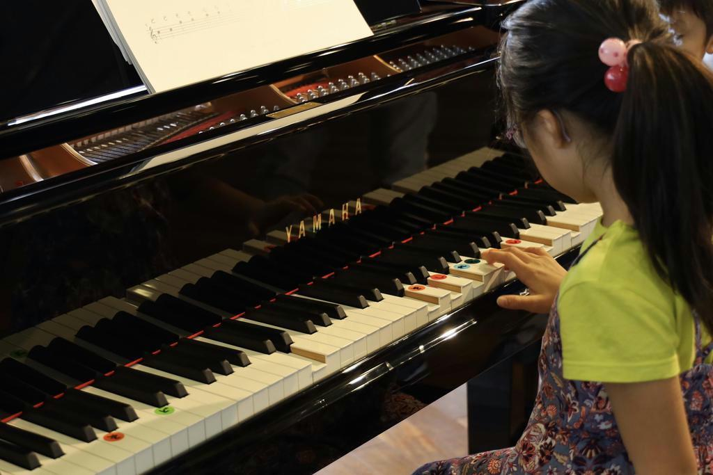 横浜音祭りでだれでもピアノを体験する女児。伴奏部分は自動で鍵盤が押下されている=6日、横浜市(石井健撮影)