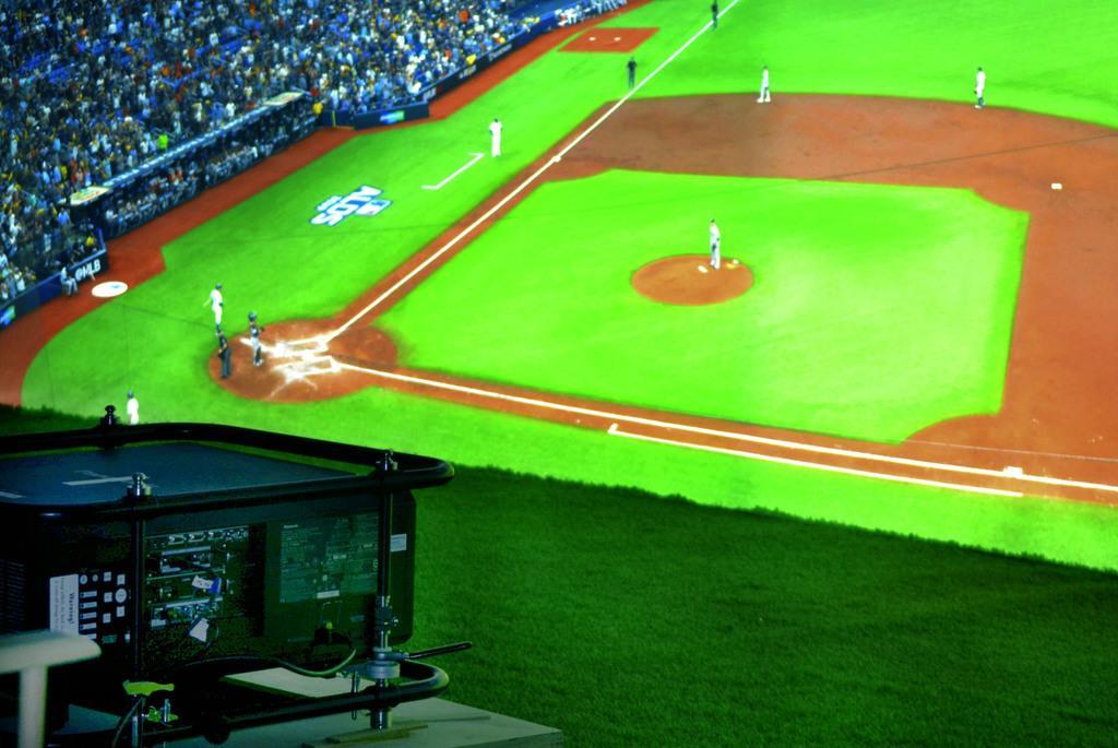 米大リーグ機構と提携したNTTが開催したイベントで、大型スクリーンに映し出されたレイズ-アストロズのア・リーグ地区シリーズの試合中継。手前は3台あるプロジェクターの一つ=7日、ニュージャージー(共同)