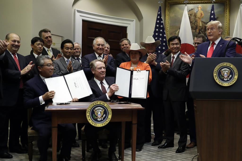 貿易協定書を見せる杉山晋輔駐米大使(前列左)とライトハイザー米通商代表(左から2人目)に拍手を送るトランプ米大統領(右)=7日、ホワイトハウス(AP)