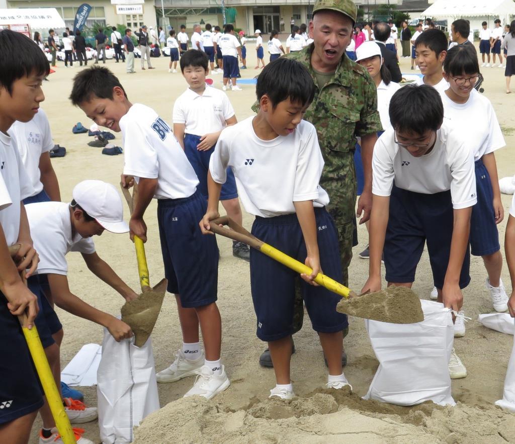 土嚢作りを体験する訓練の参加者=和歌山県有田市