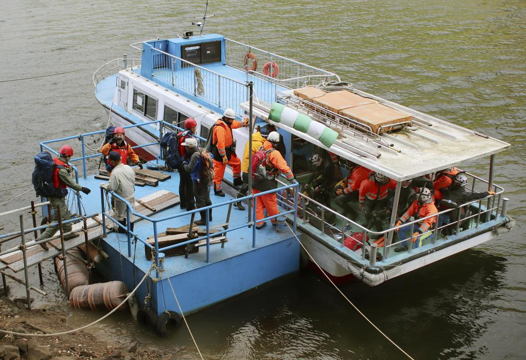 行方不明になっている地元ガイド・小野信也さんの捜索のため、船に乗り込む警察や消防の関係者ら=9日午前7時13分、秋田県北秋田市