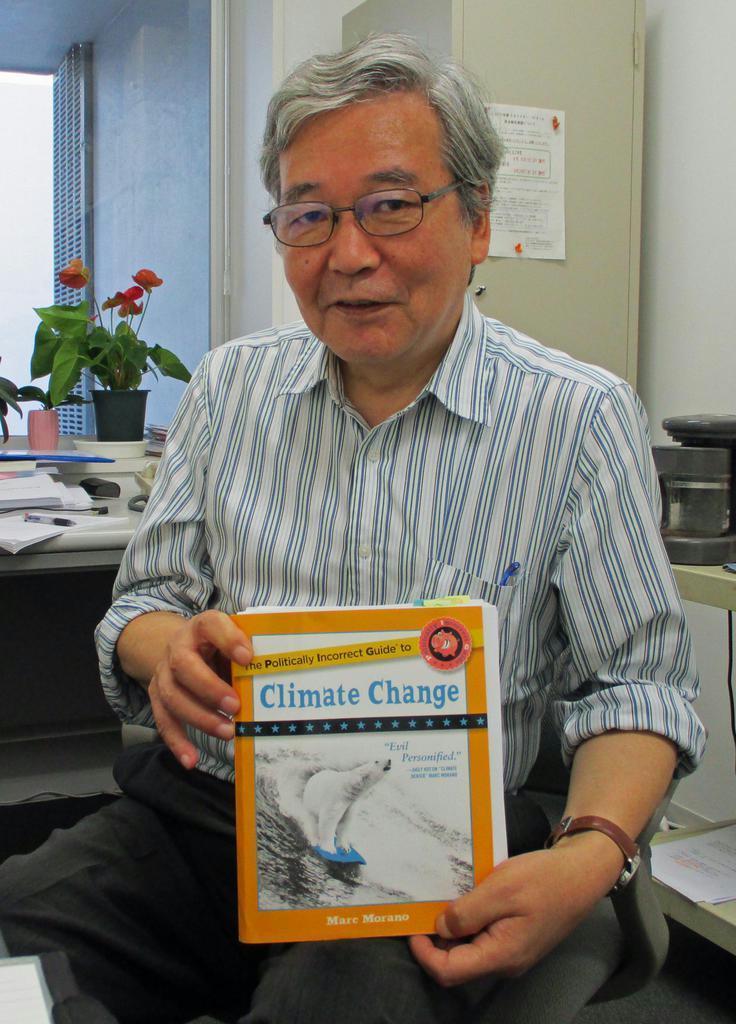 「米国では温暖化について活発な議論が戦わされているのが分かる」と話す訳者の渡辺正教授。手にしているのはベストセラーとなった原著(長辻象平撮影)
