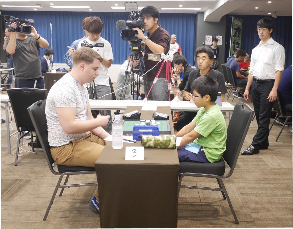 第43回世界オセロ選手権の予選がスタート。「小学生グランプリ」を勝ち抜いて出場の日本代表・薬師寺健太君(右)の対局には、メディアも注目