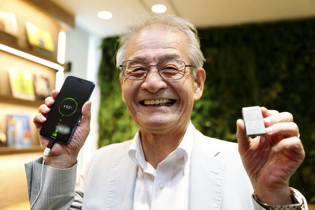 リチウムイオン電池(右)とスマートフォンを手にする旭化成名誉フェローの吉野彰氏=平成30年9月、名古屋市