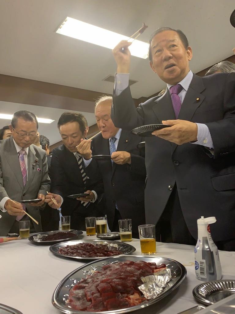 クセがなく、脂のりがいいとされるニタリクジラの刺し身を試食する自民党の二階俊博幹事長(右)=9日、自民党本部