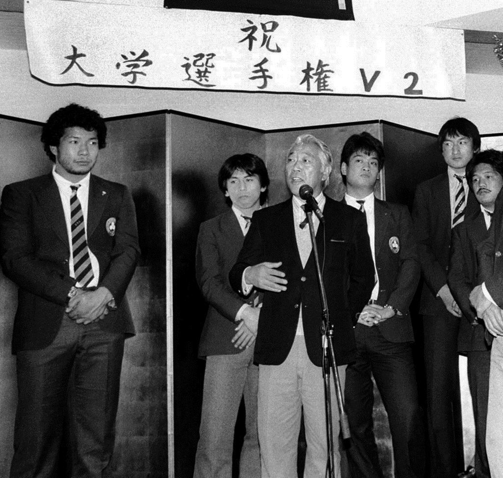 同志社大が大学選手権を2連覇したときに祝勝会であいさつする岡仁詩さん(中央)。左端は大八木淳史さん=昭和59年1月