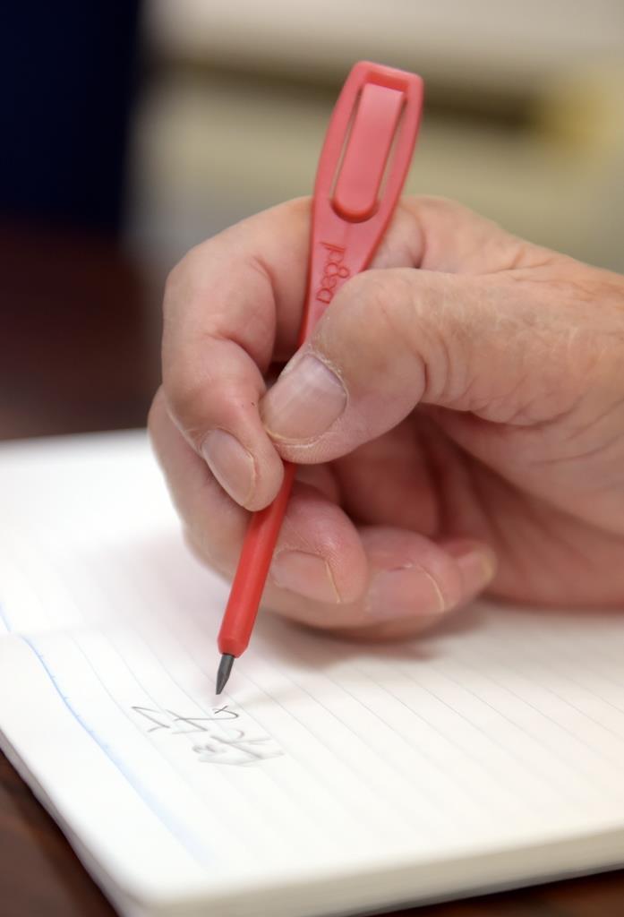 「書きやすくて折れないのがペグシルの良さ」と語る井尻和子さんの手元。ふと亡き夫、保宏さんの名前を記した=大阪市淀川区