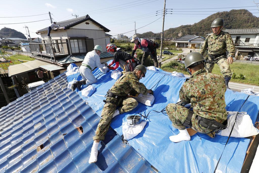 台風15号の影響で被害を受けた住宅の屋根にブルーシートを張る自衛隊員ら=17日午後、千葉県鋸南町
